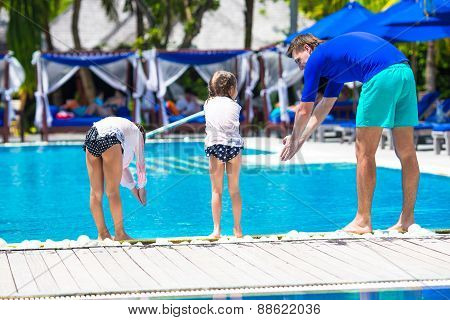 Father teaching his daughters to dive in pool on tropical resort