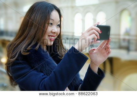 Beautiful smiling Asian girl photographed on a smartphone.