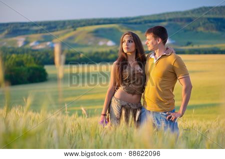 Young couple in wheat field at sunset