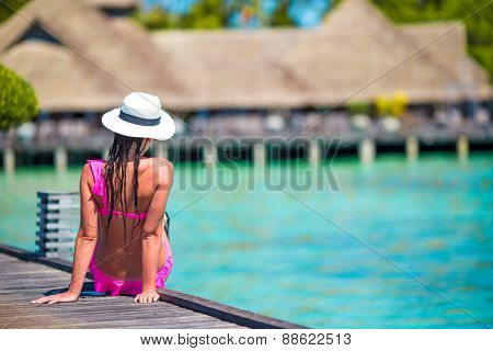 Young woman on tropical beach jetty at Maldives