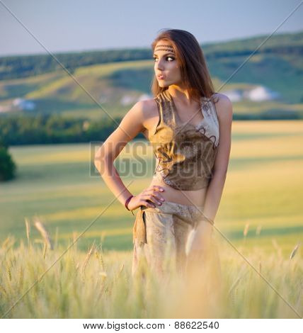 Girl in a wheat field at sunset