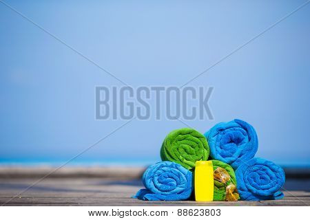 Beach and summer vacation accessories concept - colorful towels, sunglasses and sunscreen