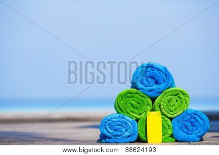 Close up of colorful towels and sunscreen bottle background the sea