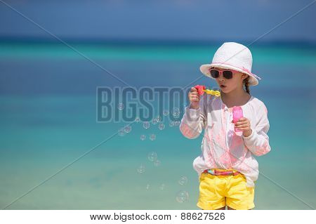 Adorable little girl blowing soap bubbles on the beach