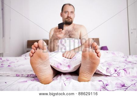 Man watching TV from the bad - close up on the feet