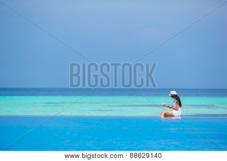 Young girl reading book near swimming pool