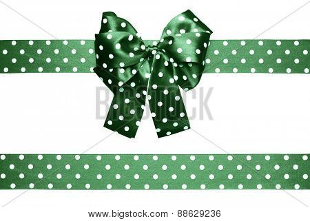 green  bow and ribbon with white polka dots made from silk isolated