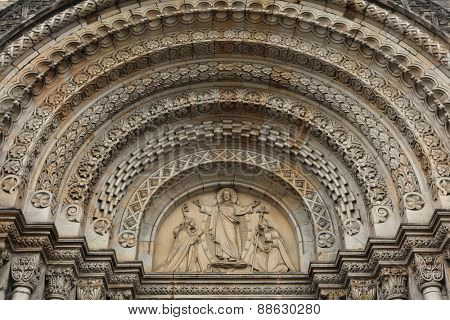 Jesus Christ blesses to Saint Cyril and Methodius. Romanesque portal of Saint Cyril and Methodius Church in Prague, Czech Republic.
