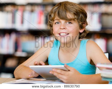Little boy sitting with tablet in library