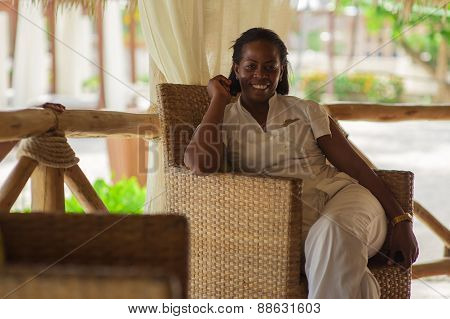 Black woman in hotel stuff uniform. Smiling stylish beautiful receptionist handing at the beach.