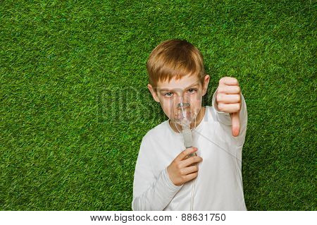 Boy breathing through inhalator mask thumb down