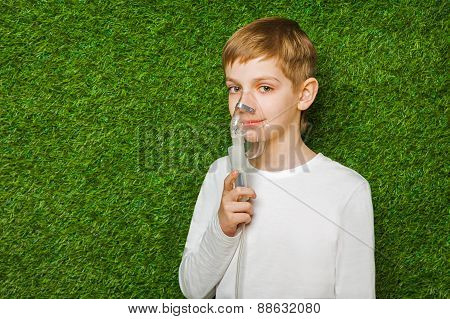 portrait of a boy breathing through inhalator mask