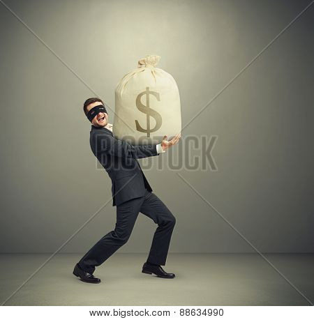 laughing man in formal wear and black mask on the eyes holding big bag with money and looking at camera against grey background