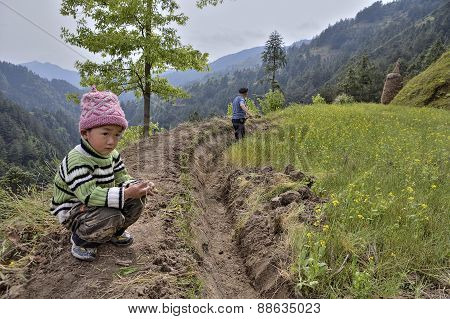 Farmer Works Soil  In Mountainous Area, Next To Boy