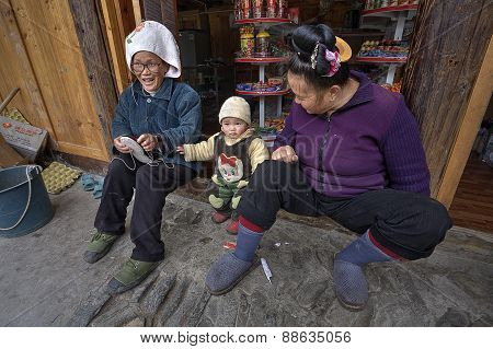 Two Asians And Year-old Child, On Threshold Of Rural Shop.