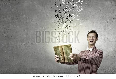 Young funny man with book in hands