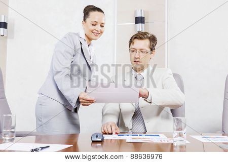 Young attractive secretary showing boss business documents