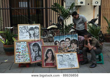 JAKARTA, INDONESIA - AUGUST 16, 2011: Street portrait painter offers his works in Old Batavia in Jakarta, Central Java, Indonesia.