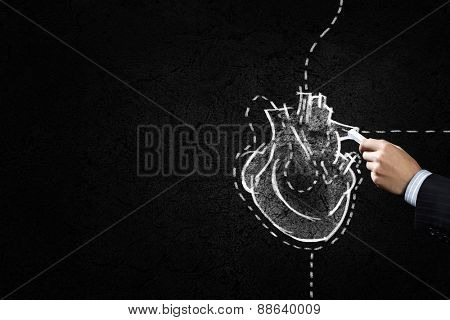 Hand drawing human heart with chalk on black