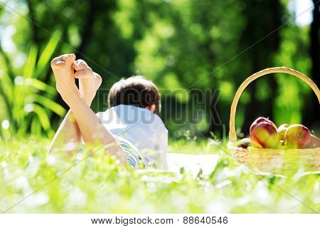 Child lying on blanket having picnic in summer park