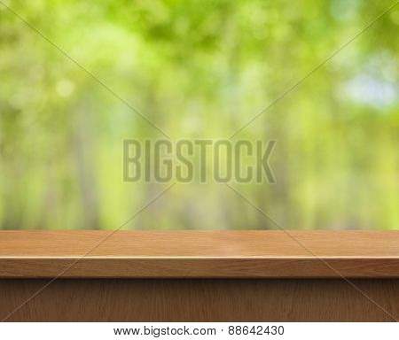 empty wood table for product display on green blurred background