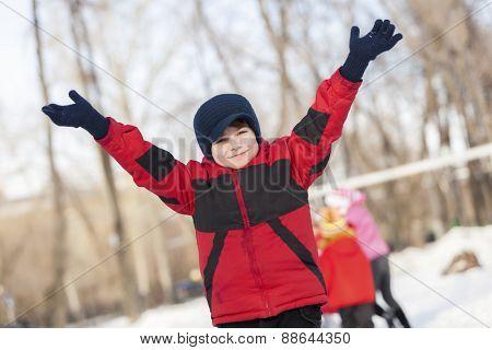 Little cute boy having fun in winter park