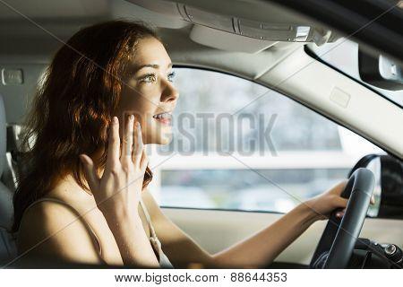 Young pretty woman in car salon sitting in car
