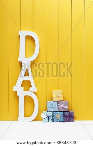 Dad Text Letters With Gift Boxes On Yellow Wooden Background