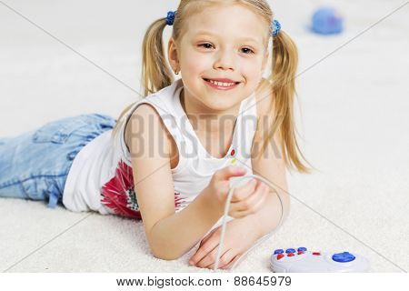 Cute girl lying on floor and playing video game