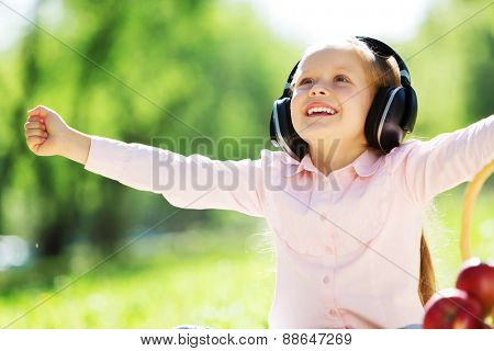 Cute girl wearing headphones sitting in summer park