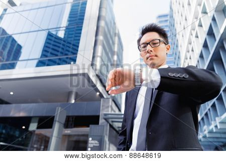 Businessman standing in street and looking at his watch