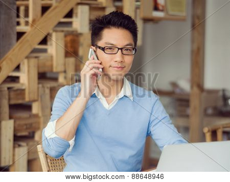 Portrait of young businessman in office holding his mobile