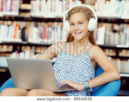 A teenage girl with headphones sitting with a laptop