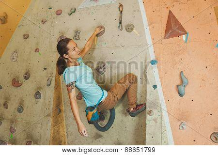 Woman Climbing Artificial Boulder Indoors