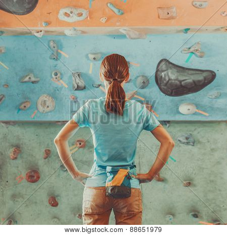 Woman Standing In Front Of A Practical Climbing Wall