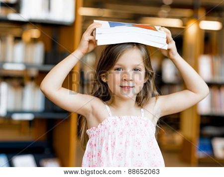 Little girl with a book on top of her head in library