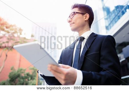 Businessman in city holding his notebook