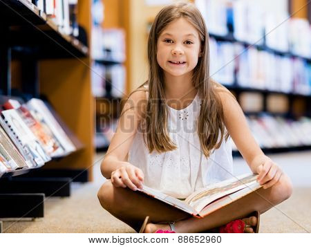 Little girl sitting on the floor and reading books in library