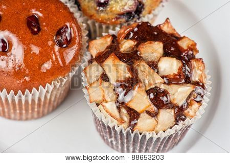 different muffins with fresh apples on white