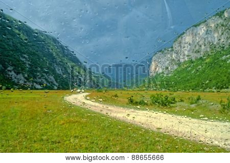 raindrops on a car glass, beyond a blurry view of the dirt road in the Komarnica Canyon, Montenegro