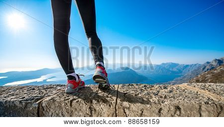 Sporty legs on the mountain hill
