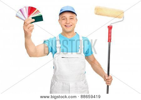 Young male painter in a white jumpsuit holding a paint roller and color guide isolated on white background