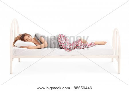 Beautiful brunette woman in pajamas sleeping in a comfortable bed isolated on white background