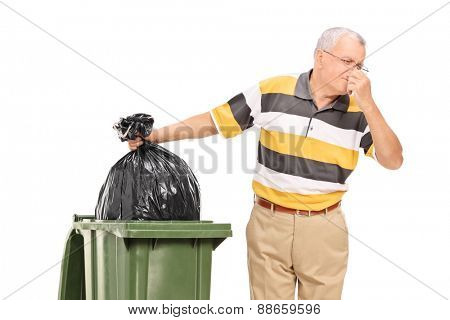 Senior throwing away a stinky bag of trash isolated on white background