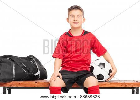 Junior soccer player sitting on a bench and holding a football isolated against white background