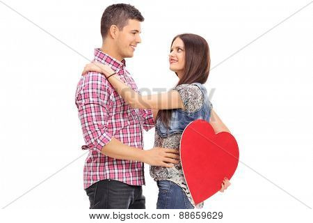 Girl holding a red heart and her boyfriend isolated on white background