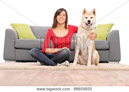 Young girl posing with her dog seated on the floor by a modern gray couch isolated on white background