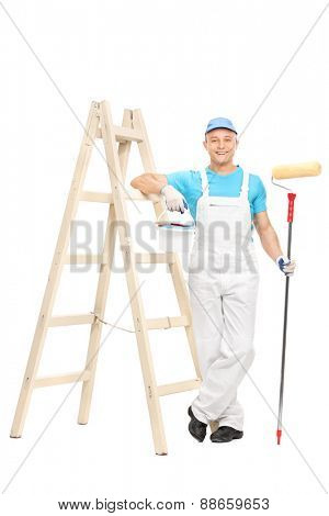 Full length portrait of a young male house painter in a white clean jumpsuit holding a paint roller and leaning on a wooden ladder isolated on white background