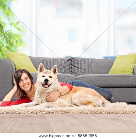 Young girl lying on the floor with her pet dog and hugging the dog by a gray couch at home shot with tilt and shift lens