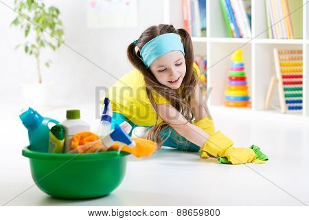 Cute little girl cleanses a floor